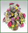 A basket centerpiece of mixed bright flowers including asters, spray mums, alstroemeria and monté casino asters.