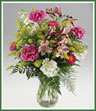 Stem length carnations, alstroemeria, stock, asters and solidaster fill a clear glass vase.