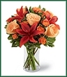 The Tigress Bouquet echoes with the fiery colors of the autumn harvest. Sweet peach roses mingle with rusted red Asiatic lilies, orange spray roses and lush greens gorgeously arranged in a clear glass vase to create a warm display of captivating color.