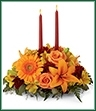The Bright Autumn Centerpiece spins the magic of the Fall season with each sun-kissed petal to set your gathering space aglow with blooming beauty.  Two taper candles are surrounded by a gorgeous arrangement consisting of orange Asiatic Lilies, gerbera daisies, and roses with golden Peruvian Lilies, burgundy cushion poms and assorted greens to create the perfect addition to your Autumn celebration.