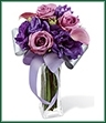 The Shades of Purple Bouquet, boasting roses and mini calla lilies, is a wonderful way to create a fantastic display of friendship and affection. Lavender roses and mini calla lilies are brought together with the deep purple of double lisianthus and beautifully arranged in a clear glass flared square vase. Accented with a lavender grosgrain ribbon, this bouquet is an ideal way to say