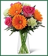 The Pure Bliss Bouquet is a blooming expression of happiness and joy set to brighten any day! Hot pink roses, orange gerbera daisies, light green carnations and lush greens are perfectly arranged in a clear gathered square glass vase to send a warm and cheerful sentiment to your special recipient.