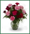 Fragrant blossoms of standard and spray carnations in a classic glass vase. Shown in pinks and burgundy, but color may vary.