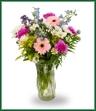 A festive mix of flowers with delphinium, peach gerbera, carnations, daisy spray mums, solidaster and tree fern.