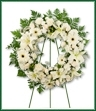 A solid all white wreath of lilies, gerberas, roses, carnations, roses and gypsophila. Appropriate for funeral home.