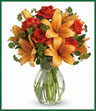 Spark someone's attention by sending this absolutely radiant bouquet. Full of flowers and fiery beauty, it makes a beautiful gift for any occasion. Features dark orange roses and orange asiatic lilies in a charming glass vase. It's fiery and it's fabulous!