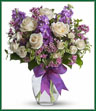 This magical bouquet will be at home in a cottage, a condo, a studio or an estate. It's so pretty it will be appreciated by all those lucky enough to receive it. Enchant someone today! White roses and spray roses, lavender stock and waxflower, all perfectly arranged in a clear glass vase that's wrapped with purple ribbon.