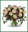 Romance blossoms beautifully within this elegant bouquet. The serenity and innocence of cream-colored roses is in delightful juxtaposition with lavender waxflower and fresh ivy greens. It's as romantic as a stroll through the English countryside. A dozen crème roses, lavender waxflower and ivy are perfectly arranged in a  glass vase.